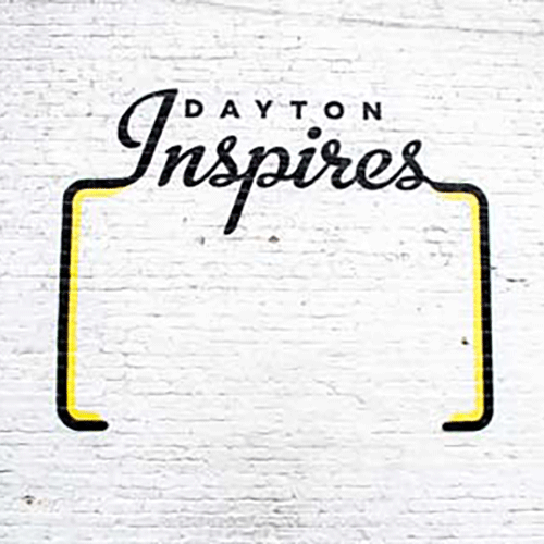 Dayton Inspires logo on white brick wall
