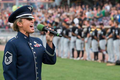 Female officer singing anthem at baseball game