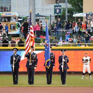 Vets holding flags at baseball game